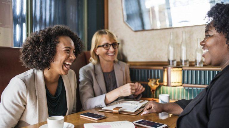 Drei Frauen lachen und unterhalten sich an einem Tisch